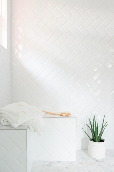 An-inexpensive-alternative-to-more-pricey-tiles-simple-subway-tiles-were-installed-in-a-herringbone-pattern-in-the-shower.-White-grout-between-the-tiles-lends-a-more-cohesive-look..jpg