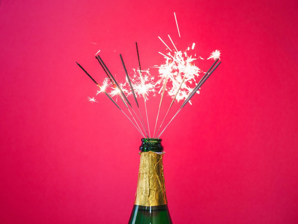 How to pick your perfect sparkling wine, choosing the perfect Champagne, champagne with sparklers on a pink background, festive sparklers and champagne, champagne bottle with sparklers