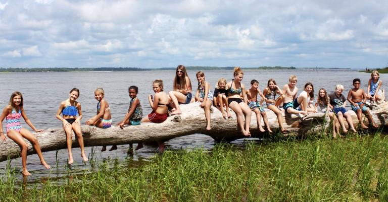 camp kids on log by water.jpg