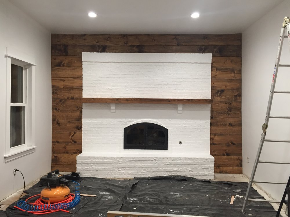 Painted the fireplace and put up a wood wall.