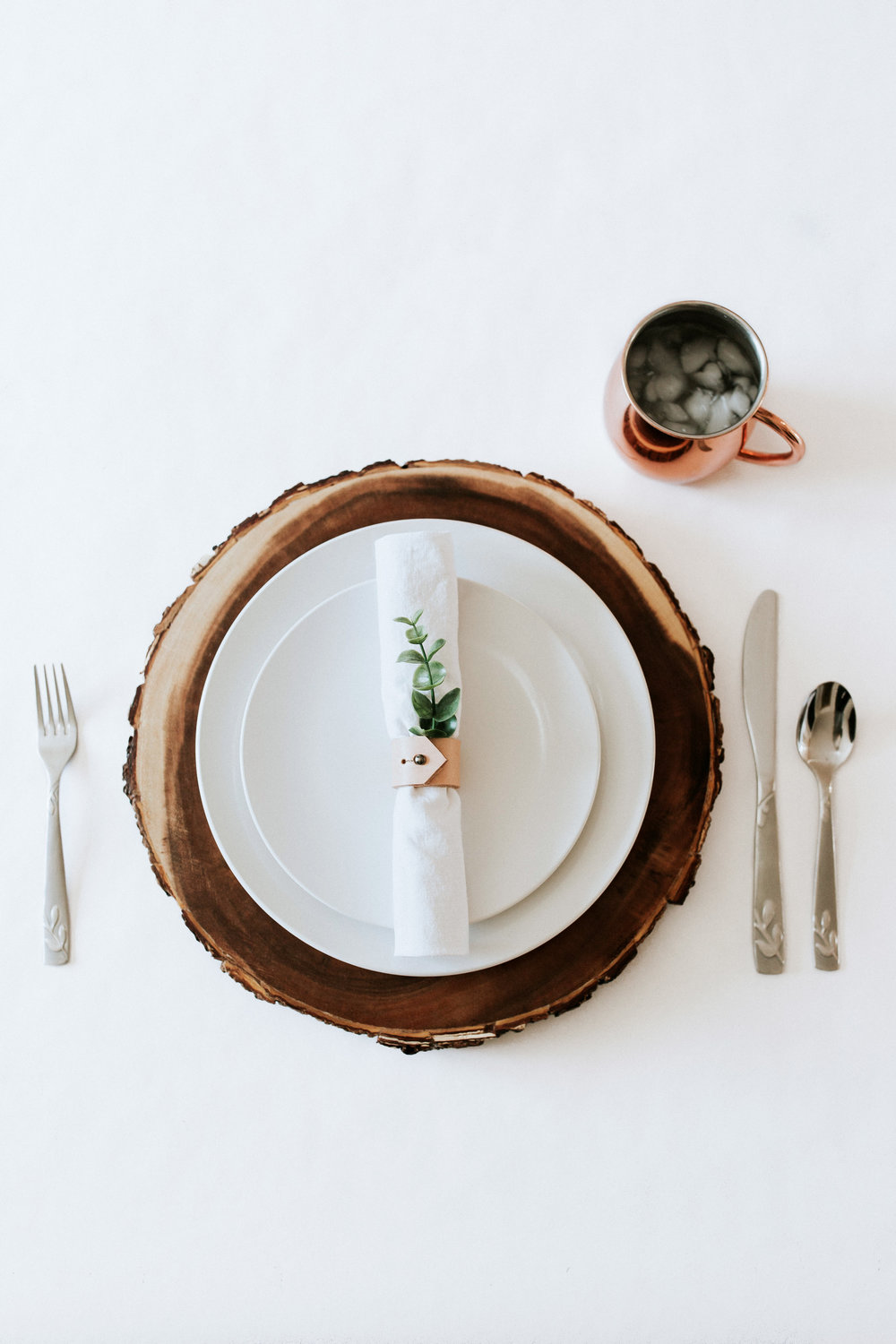 How to create / DIY a natural minimal table setting - wood charger, white plates, white napkin, leather napkin rings, greenery