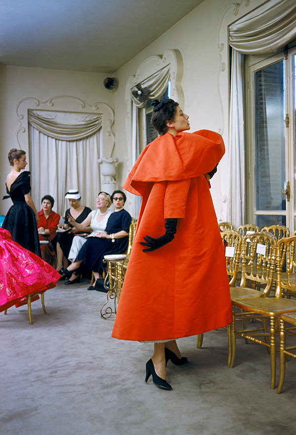 Model wearing Balenciaga orange coat as I. Magnin buyers inspect a dinner outfit in the background, Paris, France, 1954 © Mark Shaw, mptvimages.com