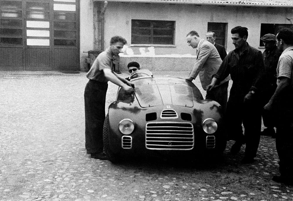 Enzo Ferrari with the 125 S in the courtyard of Fabbrica. At the wheel is Ferdinando Nando Righetti