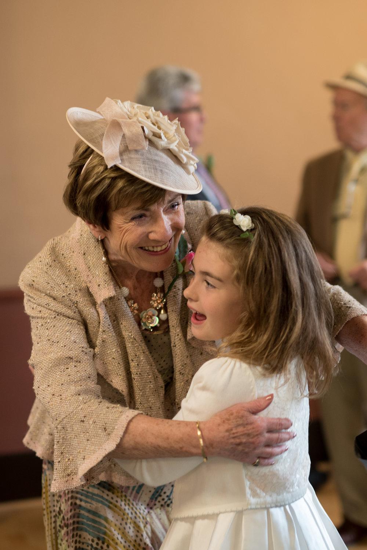 Grandmother embraces granddaughter flower girl at wedding