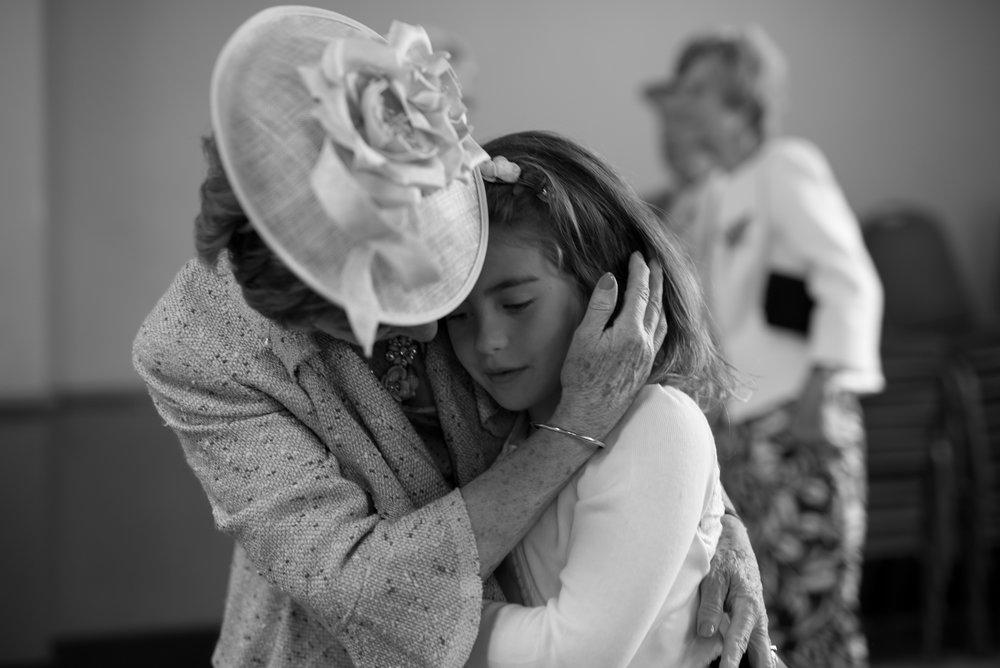 Grandmother embraces her granddaughter flower girl at wedding