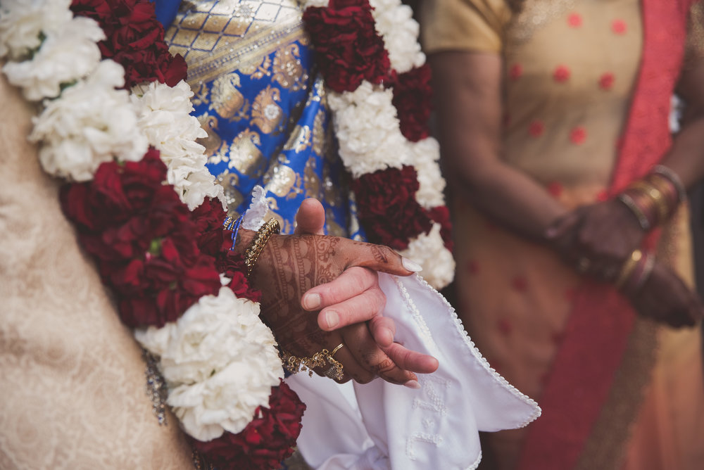 Bride and groom hold hands at Hindu wedding ceremony