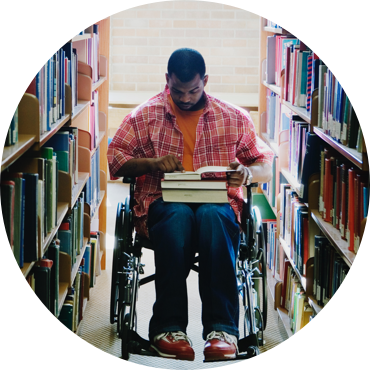 Male college student in wheelchair reading at the library