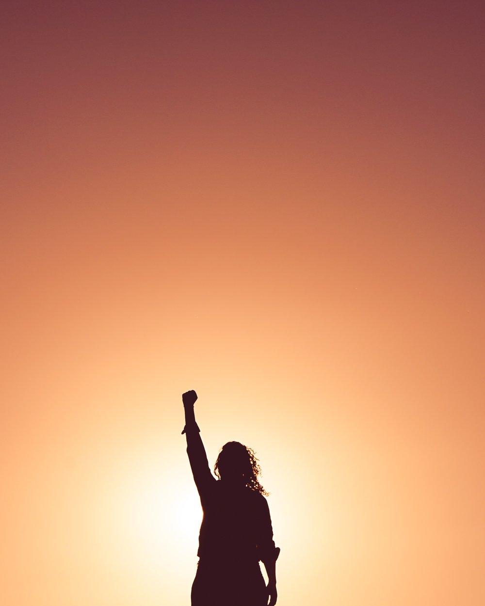 Unsplash_woman fist in air sun_miguel-bruna.jpg