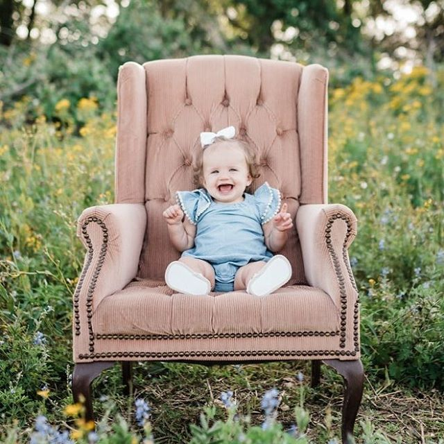 We may be a little bias but this sweet girl is the absolute cutest! Our pink wing back chair paired perfectly with the beautiful wildflowers for this photo shoot! #decorandmore #proprental #photoshoot