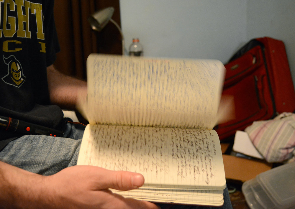 Numerous journals are scattered around Greg's small bedroom; here he flips through entries from a particularly dark time in his life as a struggling addict.