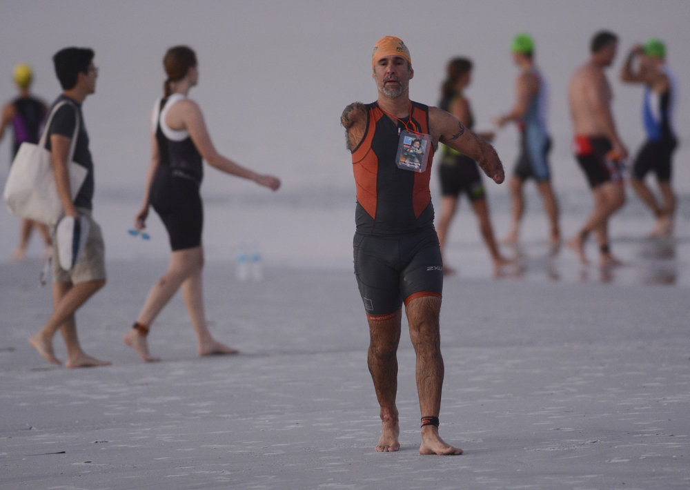 "Hector Picard of Fort Lauderdale walks across the beach after taking a practice swim in the water at Fort De Soto Park before the Tri Fort De Soto in St. Petersburg on August 21, 2016. Picard, 50, lost his arms in an accident 24 years ago. ""I'm in better shape now than I was at 26,"" he said."