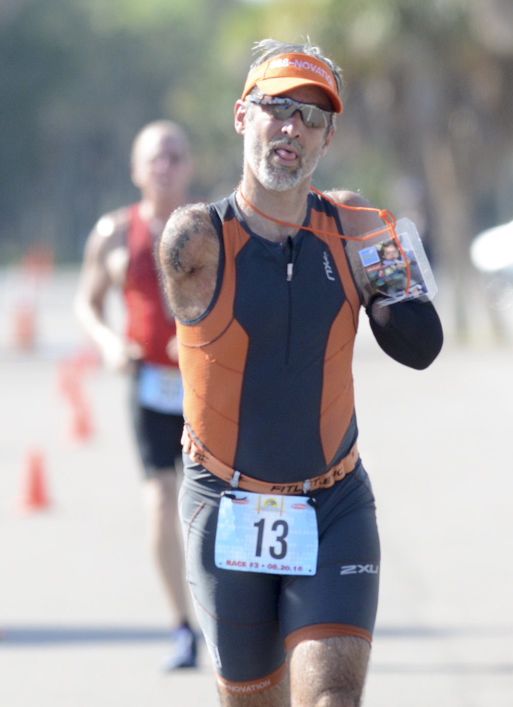 After a 1:26:46 10-kilometer run, Picard jogs the last few meters toward the finish line holding up a photo of a child at Broward Children's Center for whom he ran the triathlon. His total time in the triathlon was two hours and 46 minutes.
