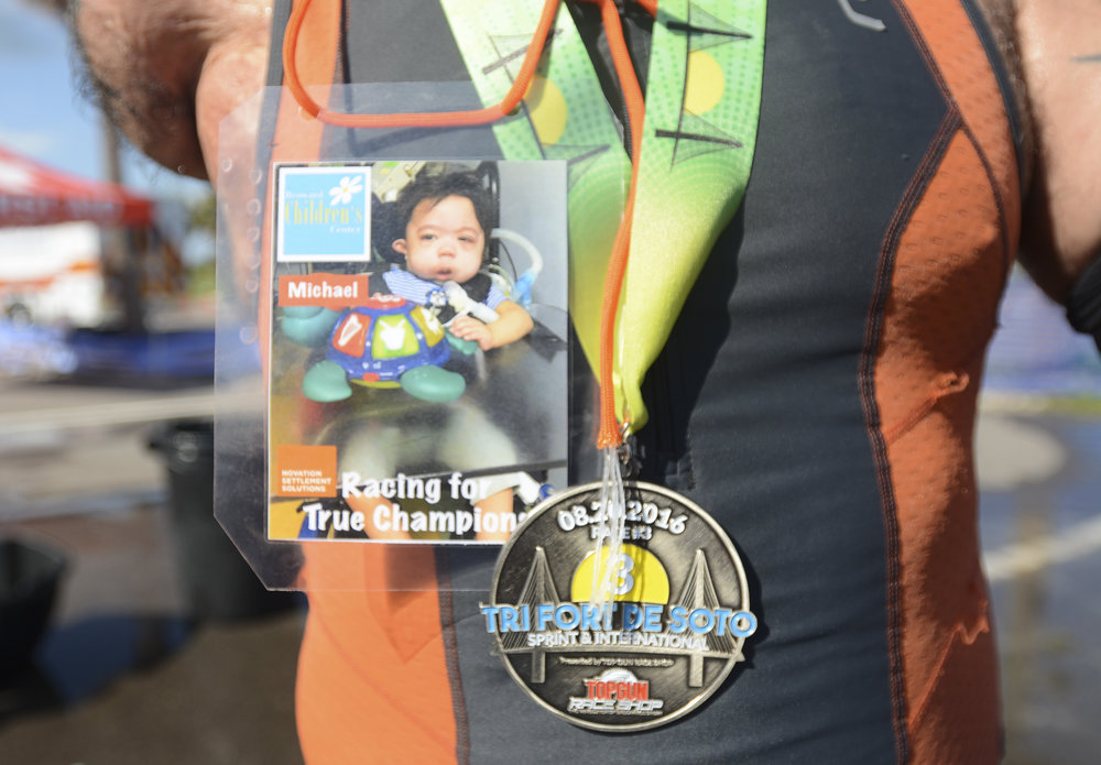 Picard competes wearing a photo of a patient at Broward Children's Center to whom he will give his race medals. He helps raise money for the center.