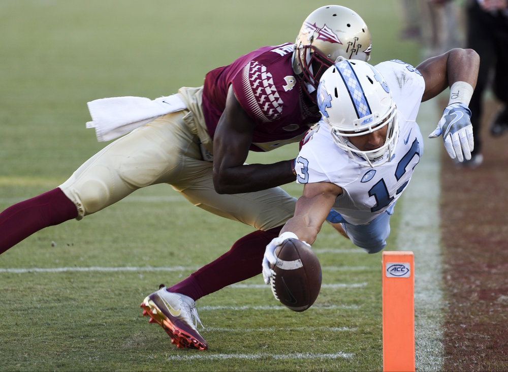 North Carolina Tar Heels wide receiver Mack Hollins (13) dives into the end zone for a touchdown past Florida State Seminoles defensive back Tarvarus McFadden (4) in the third quarter of the game between the Florida State Seminoles and the North Carolina Tar Heels in Doak Campbell Stadium in Tallahassee, Fla., on Saturday, Oct. 1, 2016. The Tar Heels defeated the Seminoles 37-35.