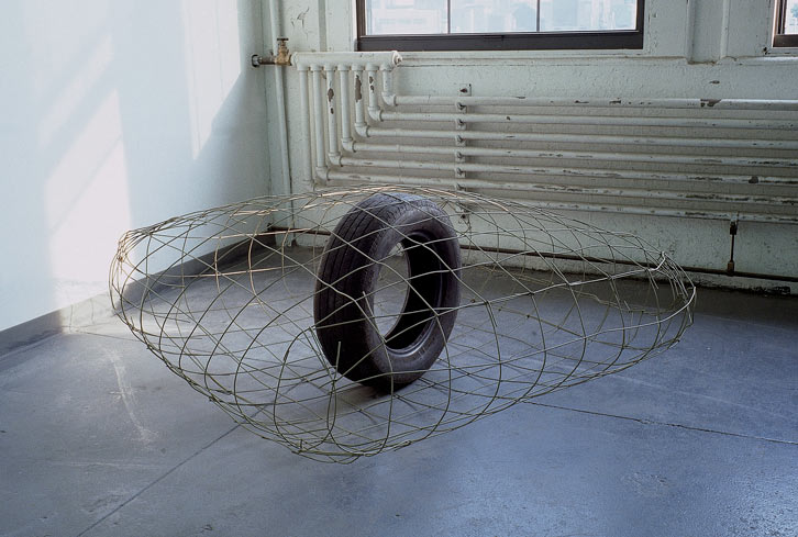 "On Road In Cloud, 2000   , rubber car tire & 6 x 6"" 11g. wire blanket   and bottles, 14 x 123 x 12 inches / 35.6 x 312.4 x 30.5 cm"