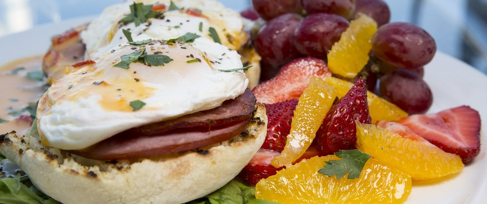 fried egg on english muffin with fruit