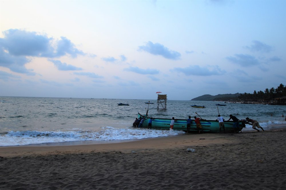 Locals Pushing the Fishing Boat to Sea