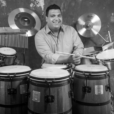 "ROBERTO QUINTERO / PERCUSSION It is hard to imagine the world of percussion without the sounds of Roberto Quintero. His loyalty and dedication to the Afro-Caribbean heritage of Venezuela has brought him a total astonishing number of 17 GRAMMY Awards. His discography includes collaborations with icons of Salsa, Latin Jazz, Pop, and Instrumental Music. Quintero has shared the stage with artists including Celine Dion, Oscar D'Leon, Marc Anthony, Paquito D'Rivera, Chucho Valdés, Gonzalo Rubalcaba, Dave Samuels Caribbean Jazz Project, Hector Martignon, Franco de Vita, Spanish Harlem Orchestra, Afro Bop Alliance Big Band, Diane Schuur, Luisito Quintero, and Juan García-Herreros, among many others. Quintero was born in Caracas, Venezuela where he grew up in one of the most renowned musical families as the son of Ricardo Quintero and Eglee Correa. At age seven he received his first lessons by his father which led him to play both the guitar and the Venezuelan cuatro. After a short period of time his great musical talent was developed and he began his studies at the Caracas Conservatory. His mentors include Jesús ""Totoño"" Blanco and Marides Mijares. With his parents' support he was able to make his first musical steps alongside some of his famous family members Nene, Chu, Rafael, and Rosalia Quintero. In Venezuela Quintero has been part of an extensive number of recordings and performances with numerous world-renowned artists, including a five-year period of touring with salsa star Oscar D'Leon. After his enormous success in his home country he decided to broaden his horizons and move to New York where he currently resides. Here he could fulfill many of his musical dreams, performing alongside countless international stars. Quintero is an extremely versatile percussionist and is able to enrich the sound of any musical genre. To date his professional studio work on percussion is documented on more than 1,000 recordings worldwide."