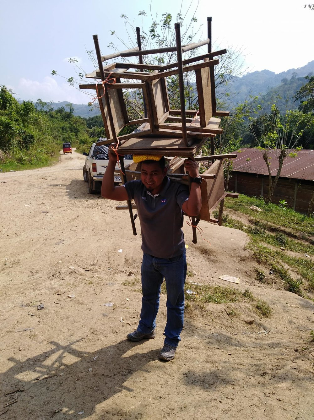 volunteers carried the desks up the mountain and across a river to bring them to the school.