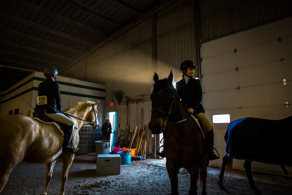 Katie Clark, left, and Isabel Gompper, right, prepare for the Open Hunter division beside the course during William Woods University Spring Fun Show in Fulton, Missouri on Saturday, Feb. 25, 2017.