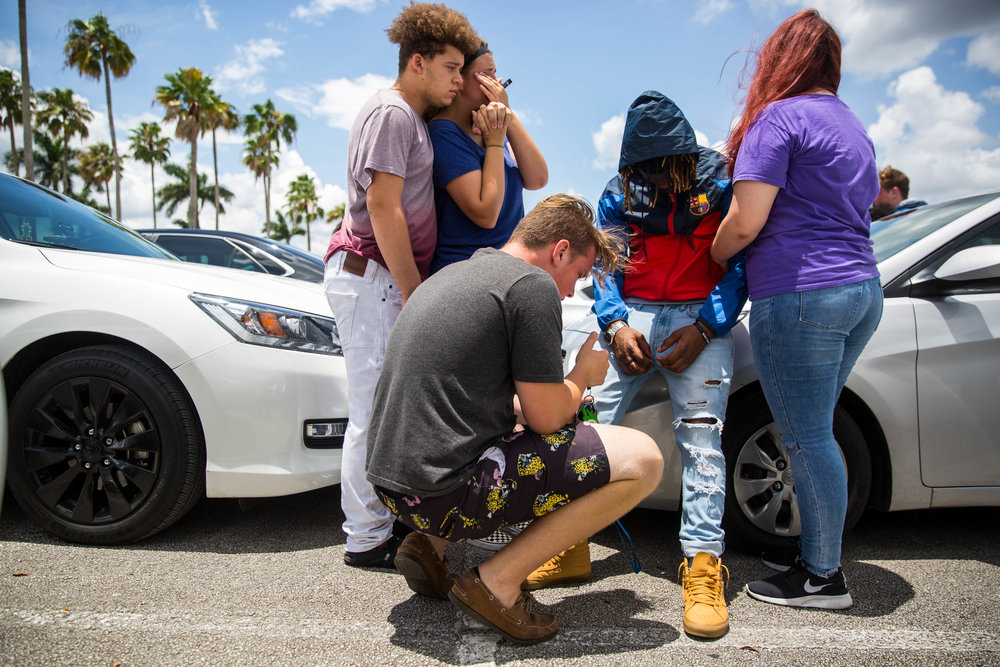 Friends comfort Sam Williams, middle, at a parking lot in front of the BB&T Center in Sunrise, Florida after the memorial for rapper XXXTentacion on Wednesday, June 27, 2018.
