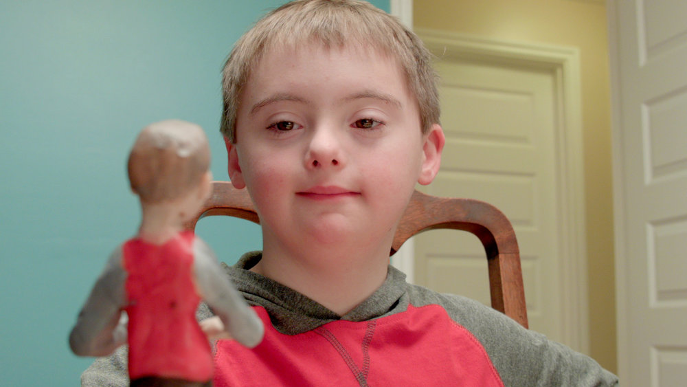 Thomas, the actor in the video, looks at a clay miniature of himself who plays in The Rockin Reef Band.