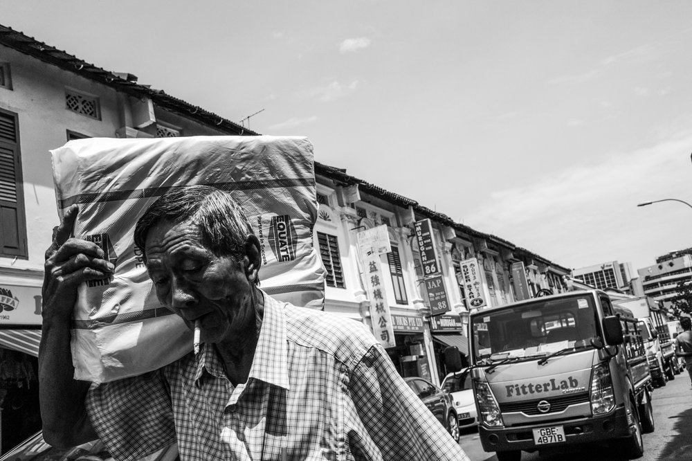 An elderly manually transports a package along a sunbaked street lined with traditional shop houses on a weekend.