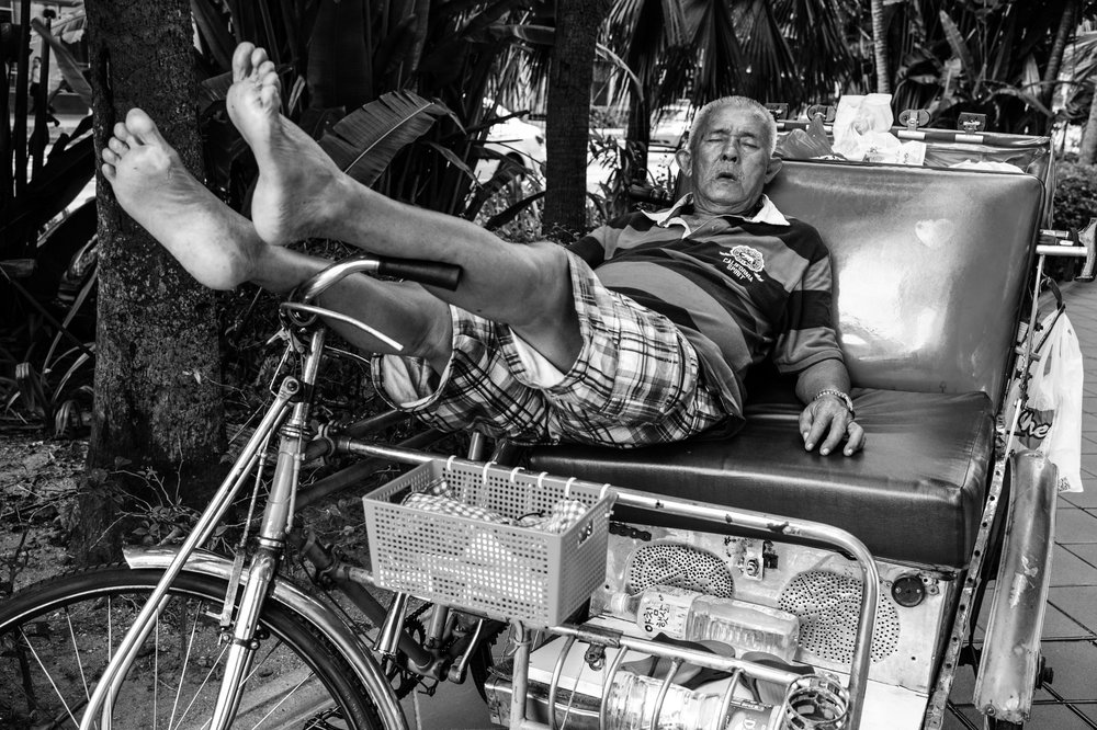 An elderly trishaw rider pauses at a sidewalk to rest his tired feet. Once a ubiquitous trade, trishaw services have dwindled significantly with the modernization of Singapore.