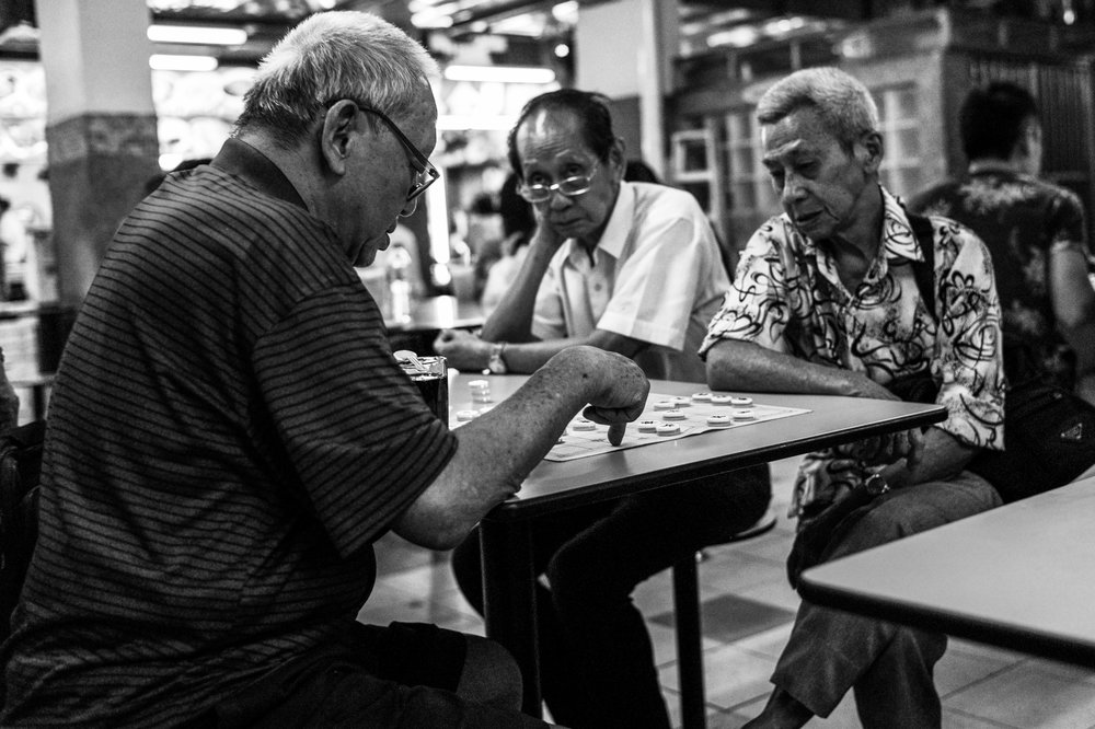 An elderly ponders his next move over a friendly game of Chinese chess in a food court.