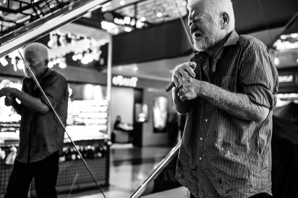 A semi-blind elderly with obvious physical afflictions wanders aimlessly and in agony in a shopping mall, with no help in sight.
