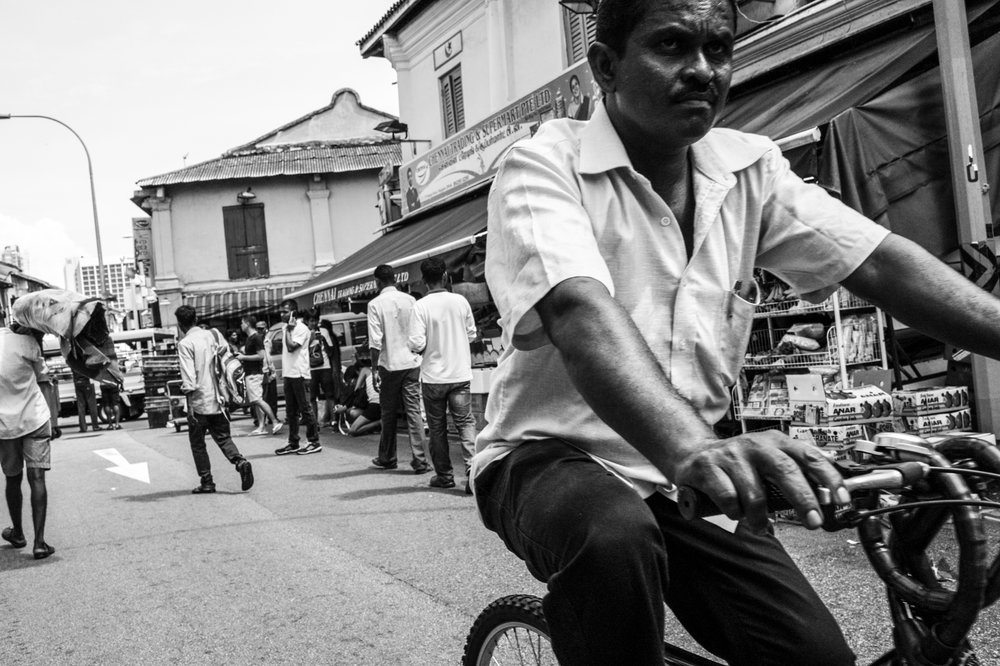Street bazaar . A cyclist passes through one of the busiest streets in Little India where food, groceries and supplies are sold and serviced mainly to migrant workers.