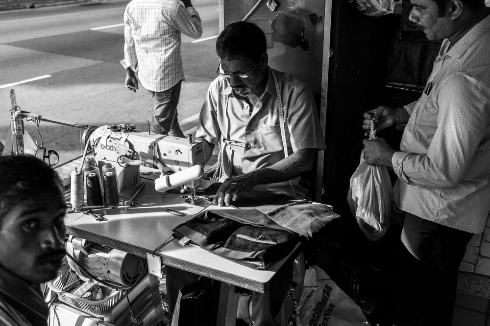 Services on a fast lane . A roadside tailor enjoys a relatively brisk business day as customers come forth to have their garments fixed.
