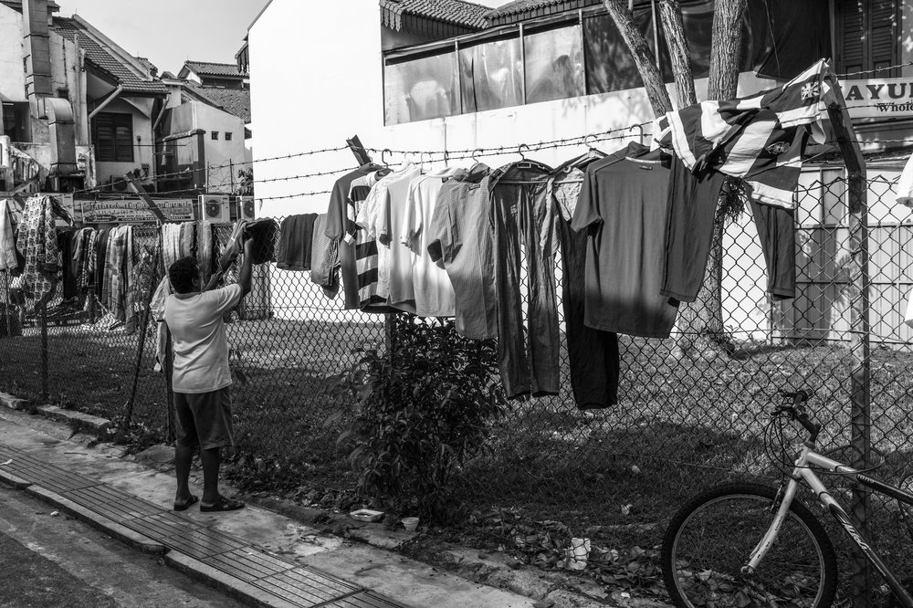 Dhoby.  A man openly airs and displays his laundry among his contemporaries' along an alleyway.