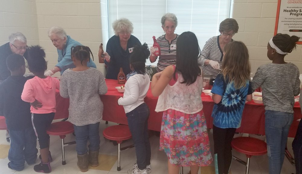 At quarterly ice cream parties, church members serve ice cream to students from First Ward Creative Arts Academy to celebrate their achievements.