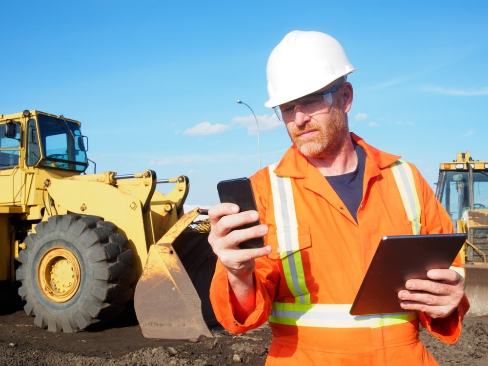 construction-worker-and-computer-and-phone-technology-picture-id532113455.jpg
