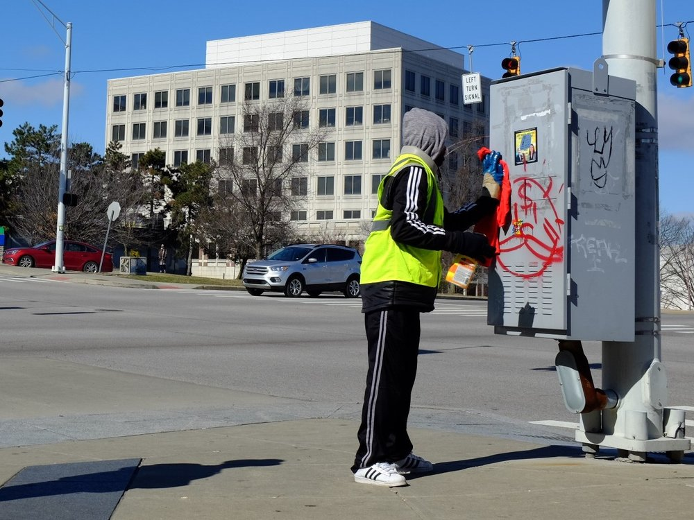 Uptown Sheriff Work Detail member removes graffiti in Uptown for Keep Cincinnati Beautiful.