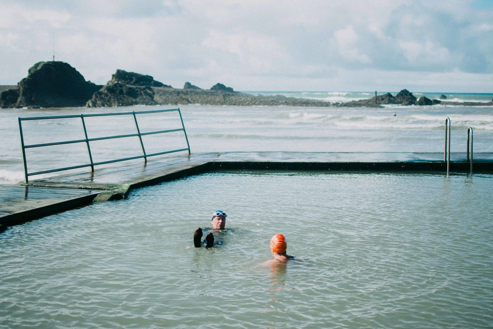 Cold water swimmers and members of Devon & Cornwall Wild Swimming, Billy O'Mahony and Katherine Short, tread water during their morning swim in Bude Sea Pool. Summerleaze Beach, Bude, Cornwall. 2017.