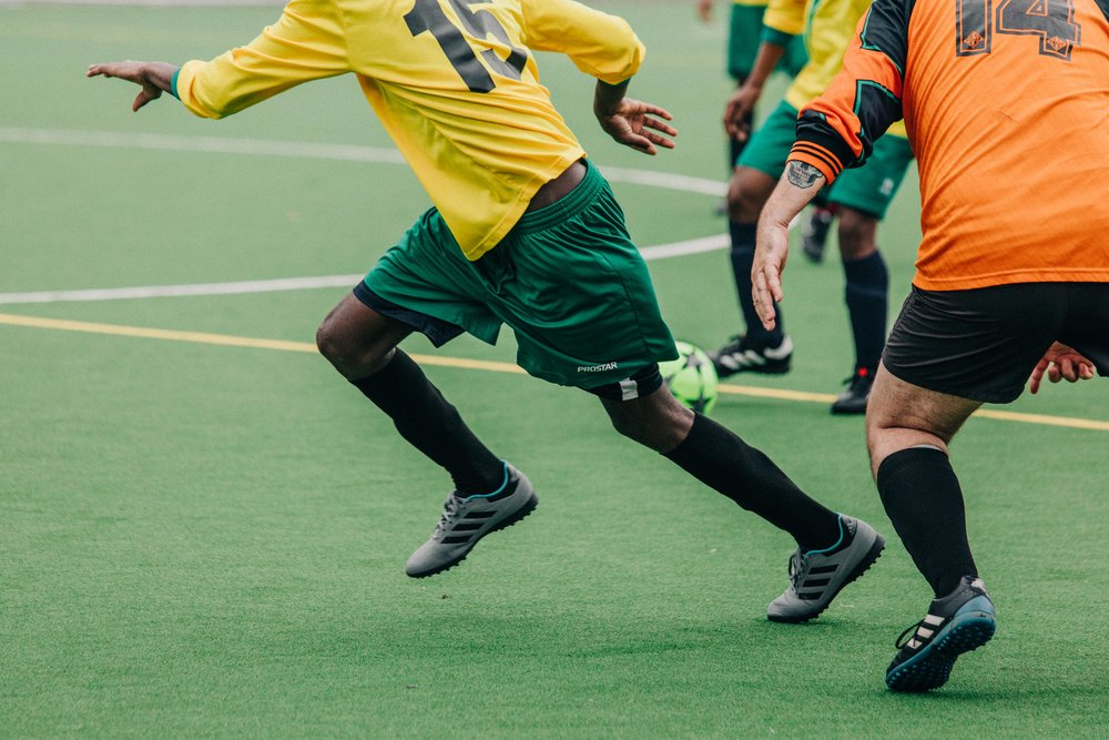 Nations United FC (yellow) during their debut game against Clancy's Cavaliers, on Chichester College football pitch. Chichester, UK. 25/03/18