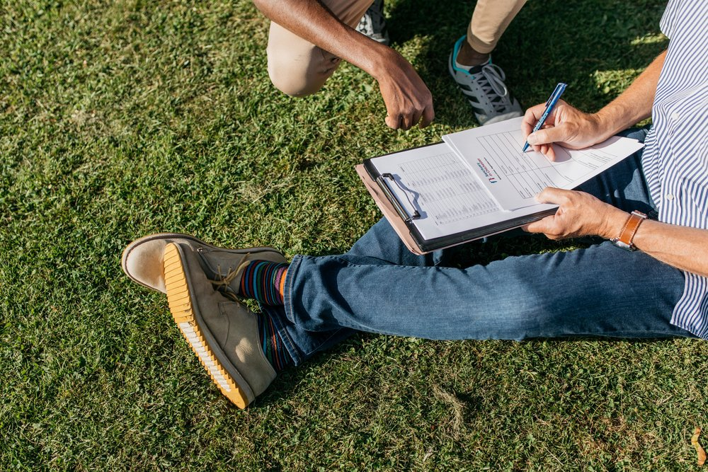 Volunteer Team Co-ordinator Steve Gough registers a player for Nations United during a training session, collecting information such as where in West Sussex they are based and contact information of their temporary guardians. Chichester University Field, Chichester, UK. 14/06/18