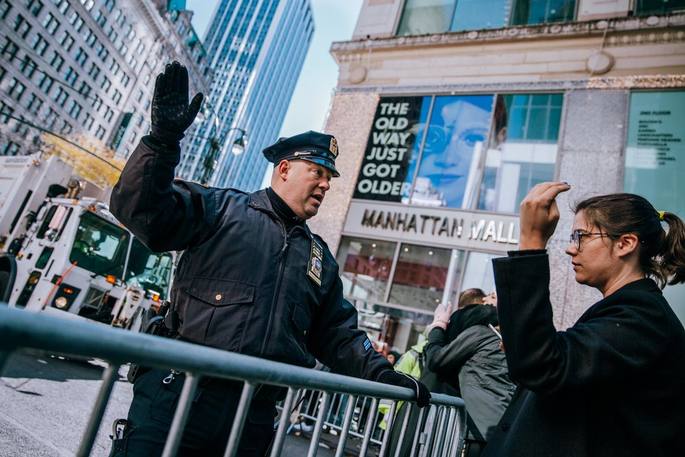 An NYPD office gives directions from behind a barrier to a woman at the Macy's Thanksgiving Day Parade. Security was heightened at the 2017 parade which came less than a month after a terrorist attack which killed 8 people. New York, USA. 23rd November 2017.