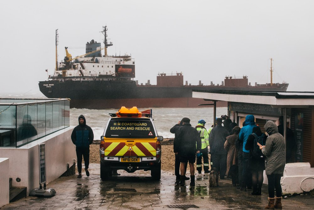 People watch in the rain as a rescue operation is carried out to refloat a Russian cargo ship which was grounded at Gyllyngvase Beach on Tuesday morning. Falmouth, Cornwall. 18th Dec 2018.