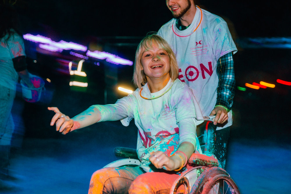 Two participants in the Night of Neon fun run cross the finish line. Night of Neon is a fundraising event organised by Cornwall Hospice Care. The event sees hundreds of runners take on the 4km tack while being covered in neon powder by volunteers along the route. Over £9000 was raised for the nursing teams at CHC's hospices in Cornwall. Flambards Theme Park, Helston, Cornwall, UK. 14th Oct 2017.