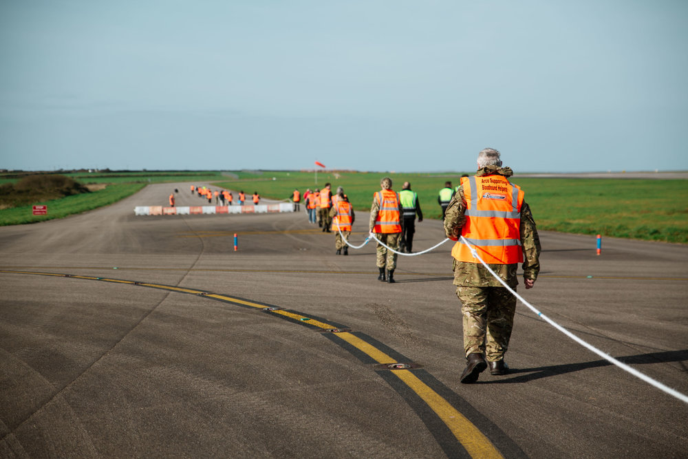 Marshals mark out a safety line for students and onlookers to stand behind during the test drive of the Bloodhound Supersonic Car on the runway of Newquay Airport, as part of the Cornwall Skills Show. Newquay, Cornwall, UK. 30th Oct 2017.