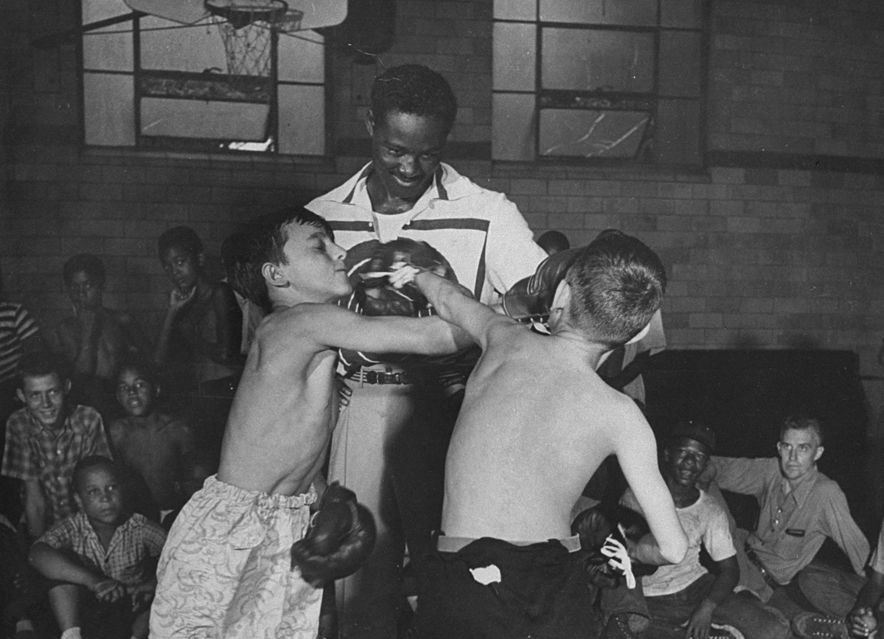 Heavyweight boxing champ Ezzard Charles refereeing 2 youths in gym of the YMCA, Cincinnati. (Photo by Norman J. Gordon/Pix Inc./The LIFE Images Collection/Getty Images)