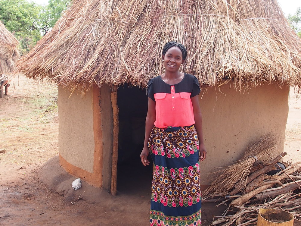 A Manchinchi villager standing in front of her new half-wall kitchen with a stack of small-diameter wood for her new improved cookstove.
