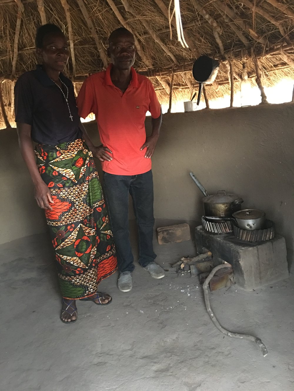 A husband and wife in Manchinchi village with a new double-pot stove and half-wall kitchen.