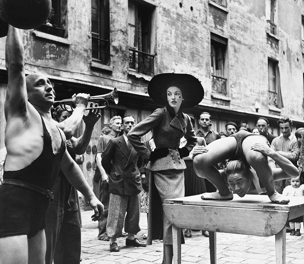 Elise Daniels with street performers, suit by Balenciaga, Le Marais, Paris, 1948. Photograph by Richard Avedon © The Richard Avedon Foundation