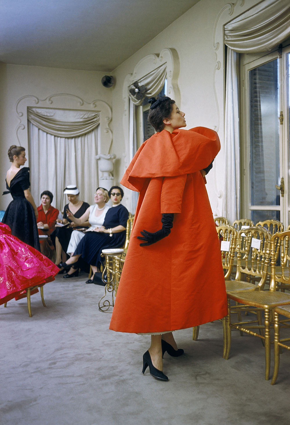 Model wearing Balenciaga orange coat as I. Magnin buyers inspect a dinner outfit in the background, Paris, France, 1954 © Mark Shaw
