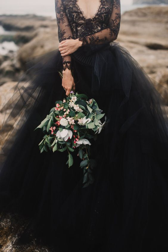 We love a classic white gorgeous gown, but this black amazing dress is making us question that! It adds a perfect element to your moody wedding and is something that different. And look at it contrasted with that gorgeous dark greenery and peach flowered bouquet, absolutely beautiful!