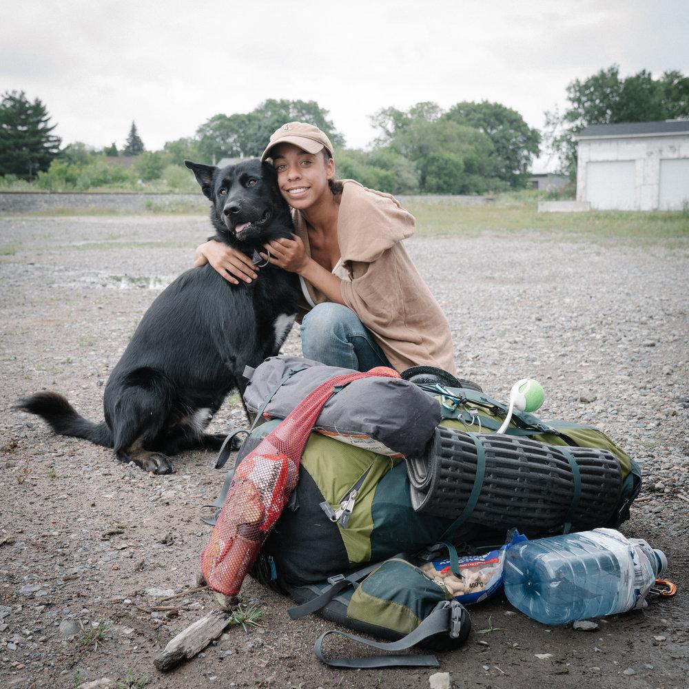 Ary, 22 ans - [ Canada : Sudbury > Winnipeg ]Originaire de Victoria sur l'île de Vancouver dans l'Ouest du Canada, Ary voyage depuis plus d'un an en stop à travers le pays avec son chien Skully. Dans son sac, une tente, quelques habits et un sac de 10 kg de croquettes pour nourrir son fidèle compagnon.Ses racines russo-barbadiennes l'ont poussé à étudier l'histoire de la Russie mais elle se voit plus travailler le bois avec ses mains dans un atelier de charpente.Sa plus grande peur est de faire face à un ours avec Skully pendant son voyage.Son année sur la route lui aura permis de rencontrer de nombreux voyageurs, surtout dans la province du Québec.